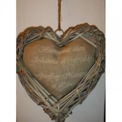 Coeur en rotin contenant un coussin sur lequel sont brodés les prénoms composant le foyer de la maison